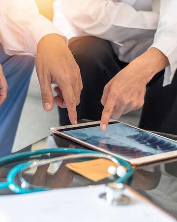 doctor teamwork diagnosing lung infection disease on chest x-ray in digital tablet with ER surgery medical team working in hospital discussing on patient care operation and treatment