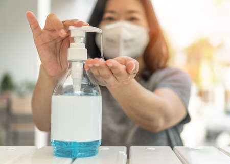 Covid-19 outbreak, coronavirus pandemic prevention with woman wearing n95 face mask cleaning hand using alcohol gel sanitizer during quarantine for hygience antibacteria safety