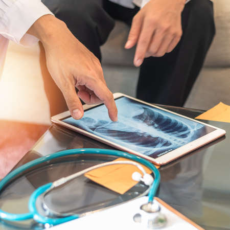 COVID-19 and doctor teamwork diagnosing lung infection disease on chest x-ray in digital tablet with ER surgery medical team working in hospital discussing on patient care operation and treatment Reklamní fotografie