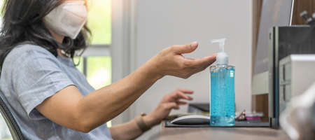 Covid-19 outbreak, coronavirus pandemic prevention with woman with n95 face mask cleaning hand with alcohol gel sanitizer during work at home quarantine for hygience antibacteria safety