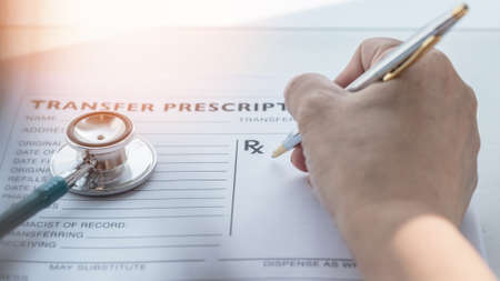 Prescription for patients medical health care record with doctor or medic pharmacist hand writing prescribing treatment in paper blank healthcare form on working desk 写真素材