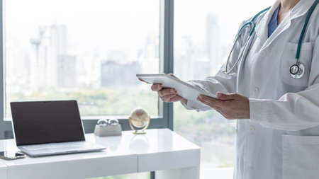 Telemedicine by medical doctor or physician consulting patient's health telehealth online using mobile tablet in hospital for professional digital emergency tele-healthcare assistance service