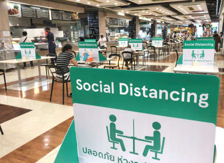 BANGKOK, THAILAND- June 21, 2020: Social distancing for COVID-19 disease pandemic prevention in Tesco Lotus food court dining table public area for keeping people distance Editorial