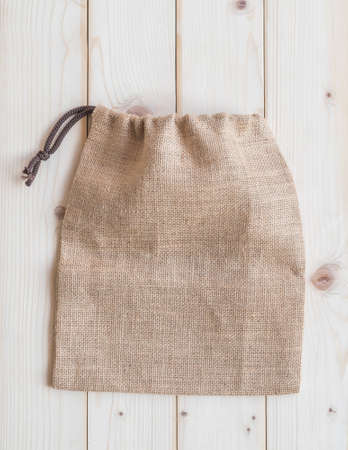 Jute hessian canvas tote bag with drawstring, mockup of small eco sack made from natural hemp burlap flat lay on white wood background from top view