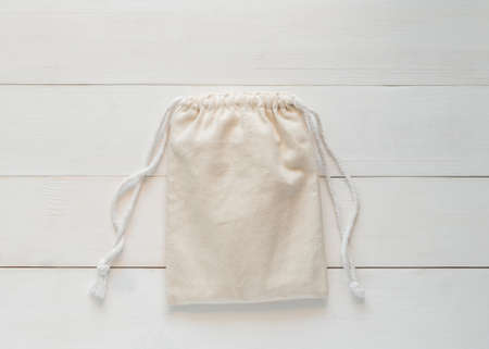 Canvas bag with drawstring, mockup of small eco sack made from natural cotton fabric cloth flat lay on white wood background from top view