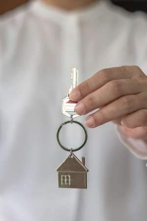 House key in real estate sale person, landlord or home Insurance broker agent's hand giving to buyer customer for new family owner, property assurance concept