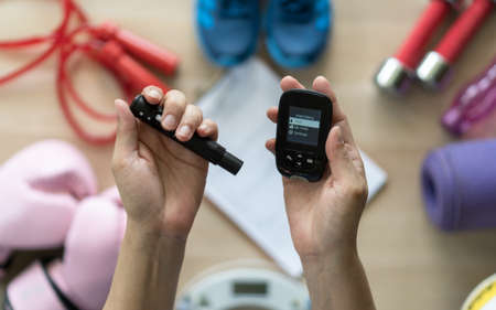 Diabetes monitoring with blood sugar test, glocuse measurement for diabetic disease awareness and control for analyzing insulin-deficient illness patient with exercise sport equipment background