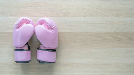 Breast cancer awareness concept with pink boxing gloves for girl and woman sports fight and recreational exercise on white wood background with copy space
