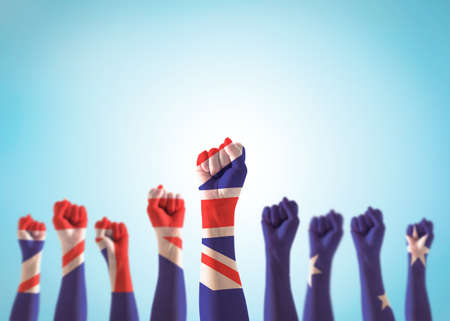 Australia labour day, Anzac day, Australian holiday concept with national flag on people fist hand raising in the air on blue sky background Stock fotó