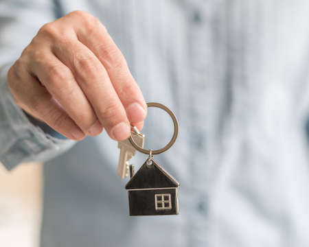 House key in real estate sale person, landlord or home Insurance broker agent's hand giving to buyer customer for new family property assurance concept 版權商用圖片