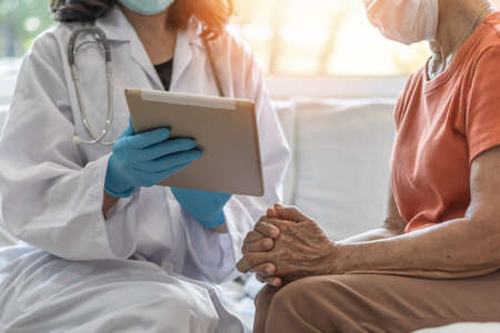 Elderly senior adult patient (older person) having geriatric doctor consulting and diagnostic examining on aging and mental health care in medical clinic office or hospital examination room
