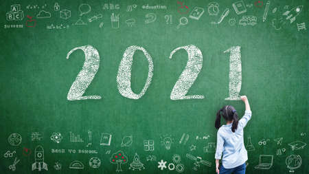 2021 Happy new year school class academic calendar with student kid's hand drawing greeting on teacher's green chalkboard for educational celebration, back to school, STEM education classroom schedule