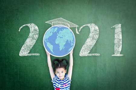 2021 new educational academic calendar year for school class with student kid raising world global planet on teacher's black chalkboard for back to school celebration, classroom schedule concept