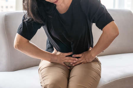 Abdominal pain in woman with stomachache illness from menstruation cramps, stomach cancer, irritable bowel syndrome, pelvic discomfort, Indigestion, Diarrhea or GERD (gastro-esophageal reflux disease) 版權商用圖片 - 157799347