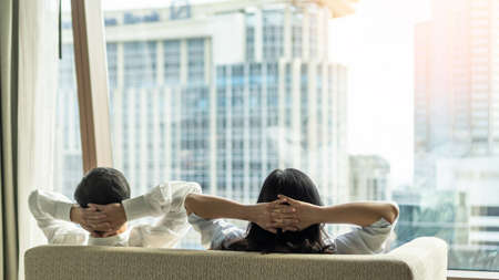 Relaxing couple lifestyle resting happily in luxury city condominium, urban condo apartment, or business hotel tower for life-work balance and living quality concept