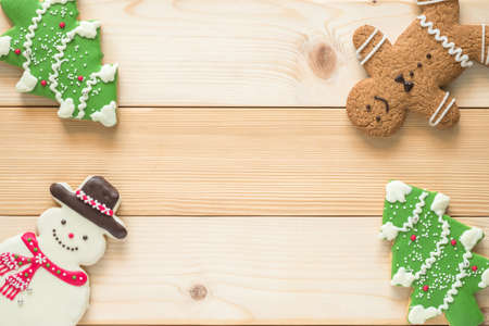 Christmas cookies, snowman, X'mas tree, gingerbread flat lay on wooden cutting board background top view for Xmas party holiday food design decoration backdrop with copy space