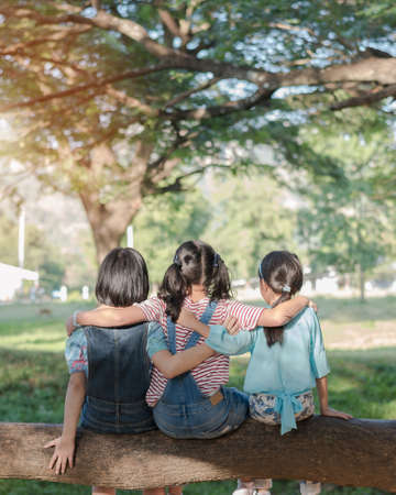 Children friendship concept with happy girl kids in the park having fun sitting under tree shade playing together enjoying good memory and moment of student lifestyle with friends in school time day Standard-Bild - 159018140