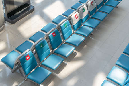Social distancing for travel safety with seat allocation and sitting distance allowance warning sign on empty chairs in airport or bus terminal during covid-19, coronavirus pandemic with no people