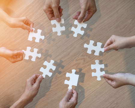 Teamwork idea brainstorming, team partnership connection for problem solving, finding solution in hope concept with puzzle jigsaw pieces in school children or student kids's hands Standard-Bild