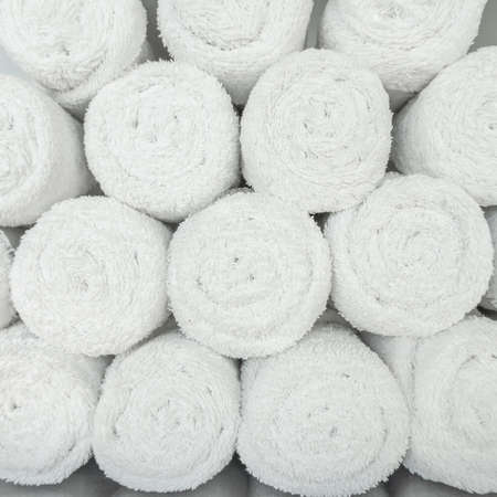 White towel roll pile in gym, swimming pool,  bathroom or spa for background