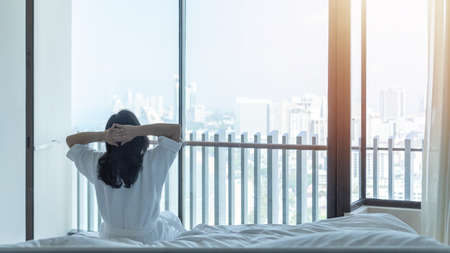 Easy lifestyle Asian woman waking up from good sleep in weekend morning taking some rest, relaxing in comfort bedroom at hotel window, having happy lazy day enjoying work-life quality balance concept Zdjęcie Seryjne