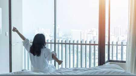 Hotel room comfort with good sleep easy relaxation lifestyle of Asian woman on bed have a nice day morning waking up, taking some rest, lazily relaxing in guest bedroom in city hotel