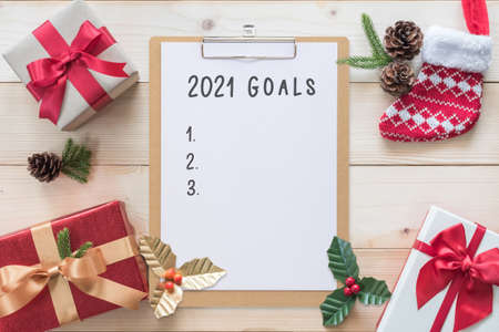 2021 Goals for new year calendar planner note on clipboard with Christmas background of gift box, red satin ribbon decoration on white pine wood, winter seasonal holiday celebration 版權商用圖片