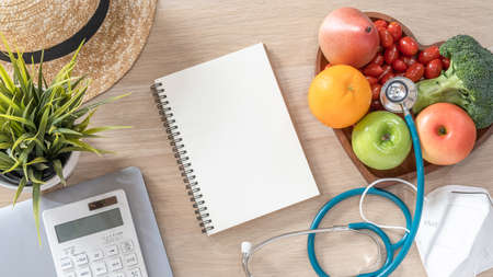 Notebook open blank note book paper page on work desk from top view with computer laptop, calculator, hat, healthy nutritious food  and safety KN95 medical face mask protection from PM2.5 Zdjęcie Seryjne