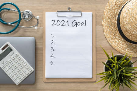 2021 goals on clipboard medical note pad for new year reminder list of yearly planner, health plan for work-life balance on desk background with computer, calculator, travel hat