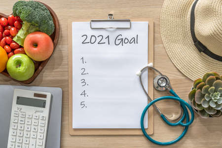 2021 goals on clipboard note pad for new year reminder list of yearly planner, health plan for work-life balance on desk with background of computer, calculator, travel hat and healthy food Zdjęcie Seryjne