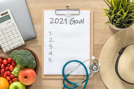 2021 goals on clipboard note pad for new year reminder list of yearly planner, health plan for work-life balance on desk with background of computer, calculator, travel hat and healthy food