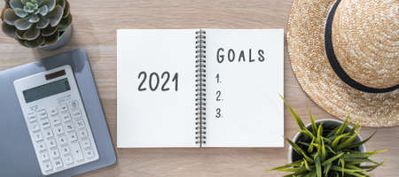 2021 goals on note book for new year memo reminder list of yearly planner, health plan for work-life balance on desk background with computer, calculator, travel hat