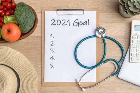 2021 goals on clipboard note pad for new year reminder list of yearly planner, health plan for work-life balance on desk with background of computer, calculator, travel hat and healthy food Standard-Bild