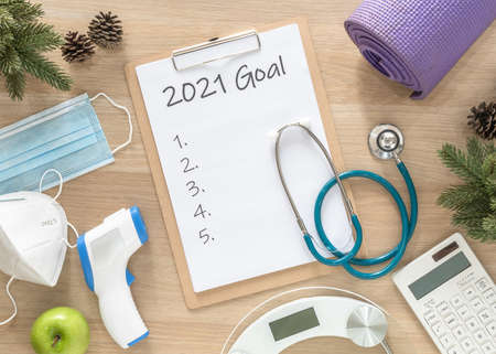 2021 new year goals in new normal lifestlye in health, covid-19 safety, weight loss, food diet, calories counting control and exercise written in white paper on medical note pad clipboard on work desk