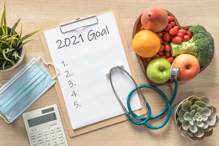 2021 New Year Goals in new normal lifestyle, work-life balance with face mask safety awareness from covid-19, healthy food, good heart health, blank resolution list on white paper medical clipboard