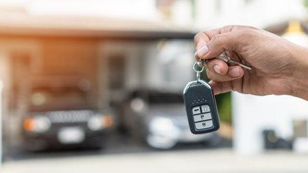 Car valet parking service enterprise, car rental, or automobile insurance business concept with owner or person handling vehicle remote key on blur parking garage background