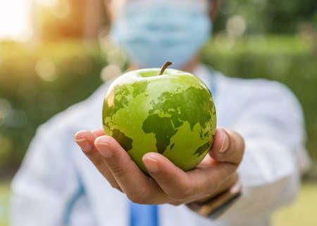 World health day, an apple a day keeps the doctor away concept for health benefit by eating high nutritious clean food and healthy nutritional diet with doctor handling green apple giving to patient