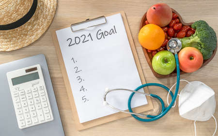 2021 New Year Goals in new normal lifestyle, work-life balance with face mask safety from covid-19, healthy food, cholesterol diet, good heart health, blank resolution list on white paper medical notepad