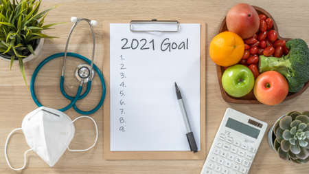 2021 New Year Goals in new normal lifestyle, work-life balance with face mask safety from covid-19, healthy  cholesterol diet food, good heart health on blank resolution list on paper medical notepad 版權商用圖片