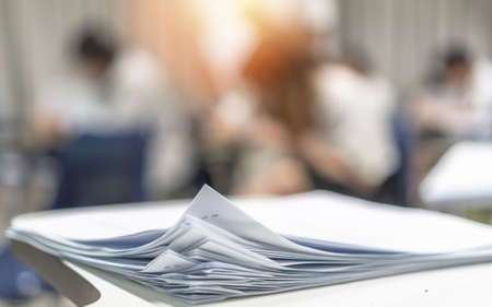 Exam answer sheet pile, blurry application document paperwork stack on office work table in examination room or classroom with blur education background school class university students taking test