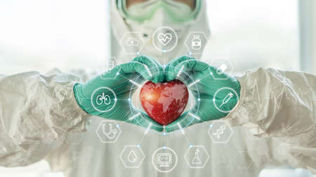 Medical technology, global health tech and world heart health day concept with cardiologist doctor in ppe for protection holding heart in hospital cardiac lab for laboratory science research