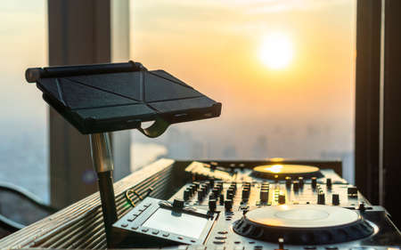 DJ Disc Jockey controller for rooftop party, luxury restaurant dinner and night club house audio entertainment on evening sunset city view background with digital tablet stand of music file