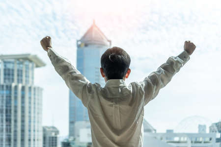 Business achievement ambition concept with businessman raising fists happily, relaxing in office or hotel room, resting and looking forward to city building urban scene Zdjęcie Seryjne