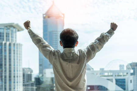 Business achievement ambition concept with businessman raising fists happily, relaxing in office or hotel room, resting and looking forward to city building urban scene Stock Photo