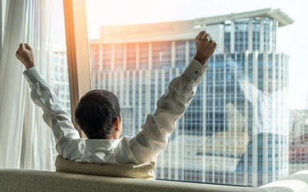 Business achievement ambition concept with businessman raising fists happily, relaxing in office or hotel room, resting and looking forward to city building urban scene 版權商用圖片