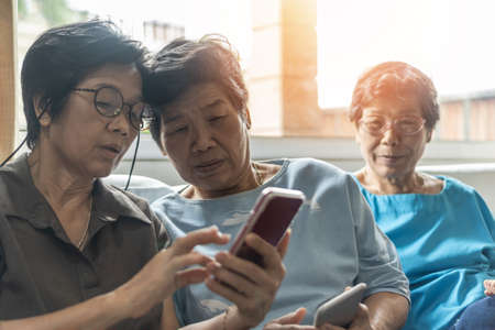 Aging society concept with Asian elderly senior adult women sisters using mobile digital smart phone application technology for social media network among friends community via internet communication
