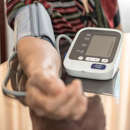 High blood pressure, hypertension and cardiovascular disease in aged senior older elderly woman with bp, heart rate, digital pulse check equipment for medical geriatric awareness in heart stroke