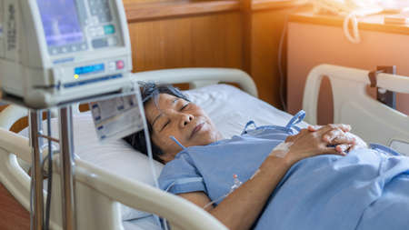 Hospitalized elderly patient senior woman sleeping on bed in hospital ward room with iv medical infusion pump infusing saline solution fluids, medication medicine for health treatment recovery
