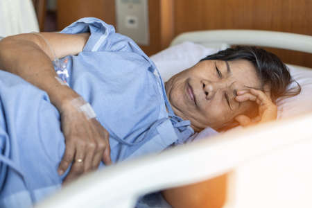 Dementia, brain injury, Alzheimer's disease or age-related neurodegenerative disorders in elderly senior aged patient hospitalized on bed in hospital for medical geriatic care and treatment Stock Photo