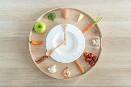 Intermittent fasting diet concept with 8-hour clock timer for eating nutritional or keto low carb, high protien food meal healthy dish and 16-hour skipping meal for weight loss